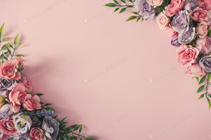 Creative arrangement of colorful flowers on pink background. Spring nature flat lay.
