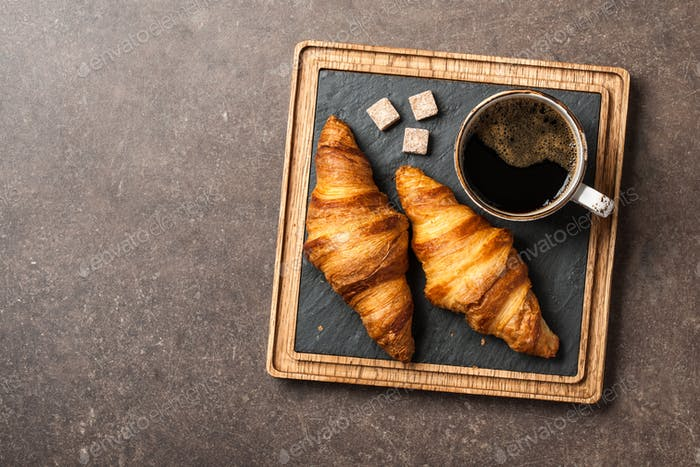 Morning black coffee with croissants on serving board