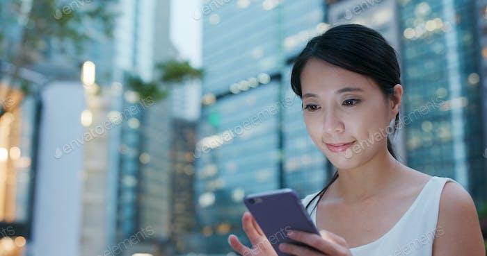 Frau Gebrauch von Handy in der Stadt in der Nacht