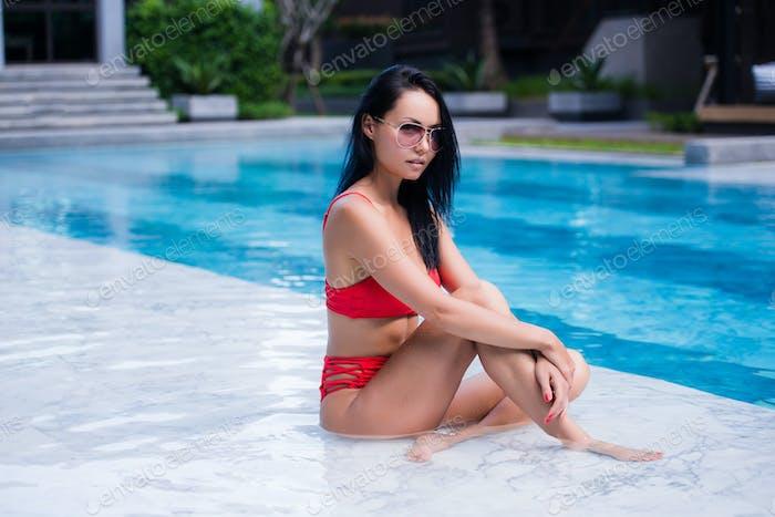 Nahaufnahme Lifestyle-Porträt von Nette Mädchen Schwimmen im Pool, Reisen und genießen Sie ihren Sommerurlaub