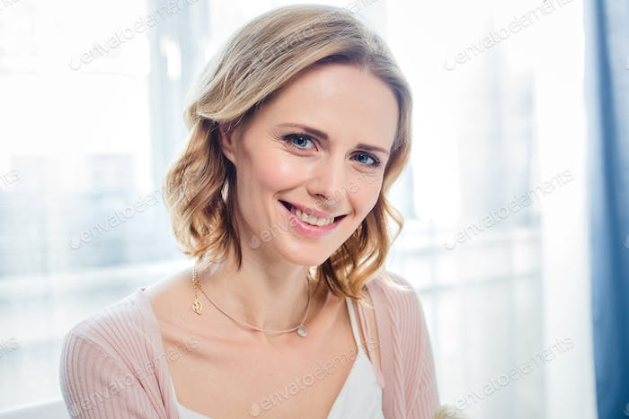 Close-up portrait of attractive young woman smiling at camera