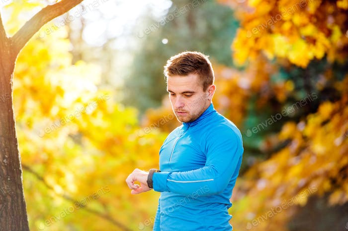 Runner in autumn nature measuring time with his watch