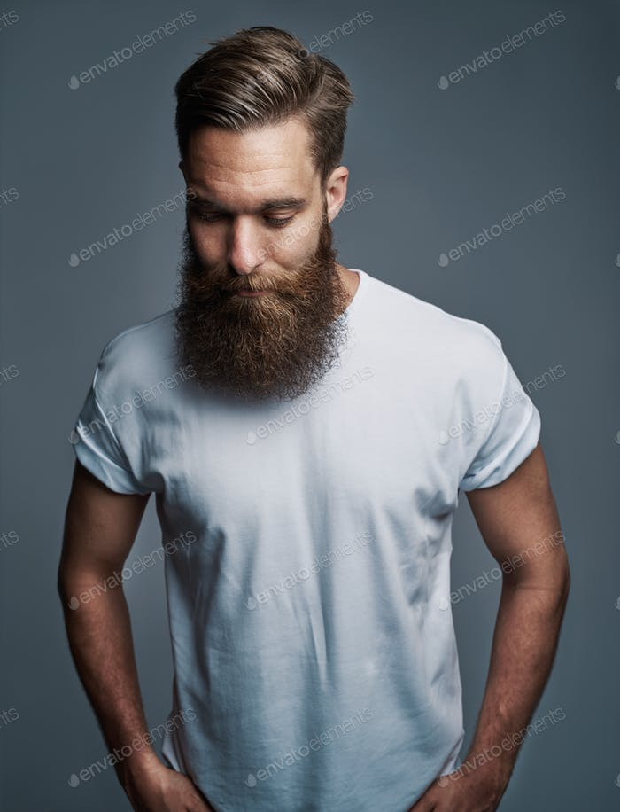 Bearded young man standing alone against a gray background