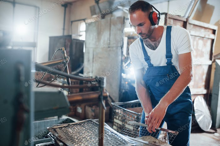 Safety of hearing. Man in uniform works on the production. Industrial modern technology