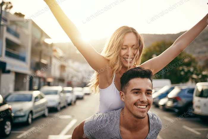 Man giving his laughing girlfriend a piggyback in the city