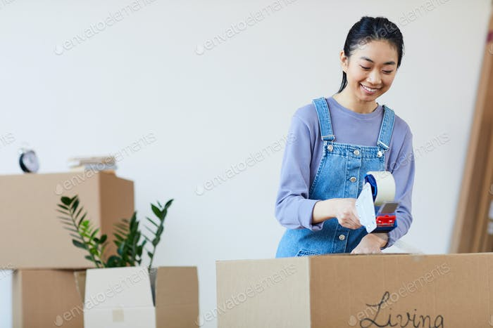 Young Asian Woman Packing Boxes for Moving