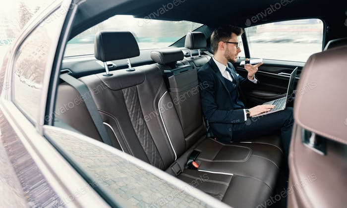Young businessman talking on phone in luxury car