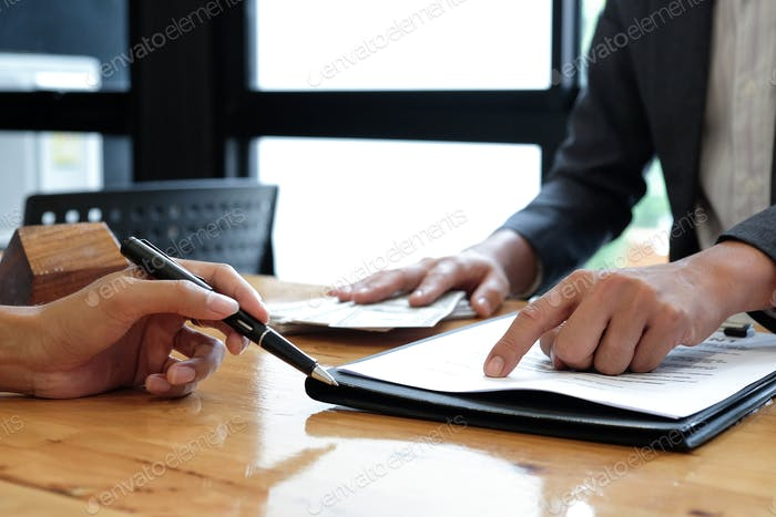 Real estate brokers pointed to signing agreement documents.
