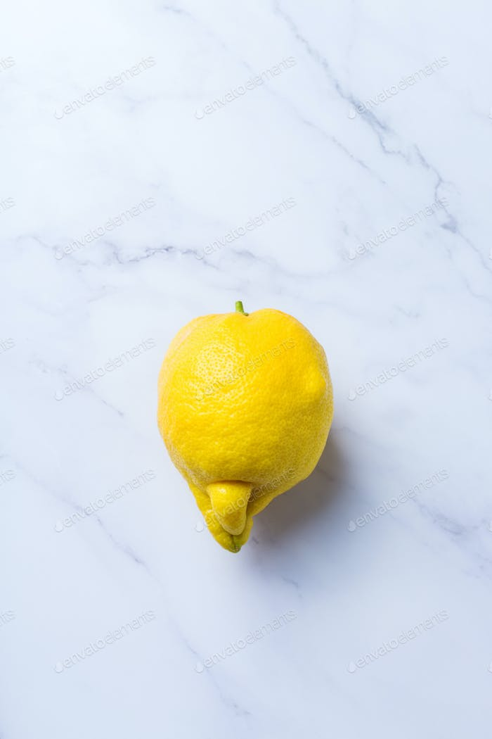 Trendy ugly fruit, yellow lemon on a table