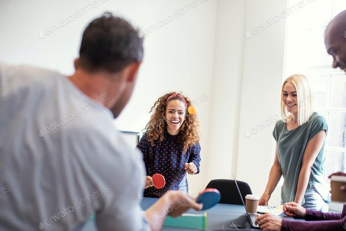 Colleagues laughing while playing table tennis together in an office