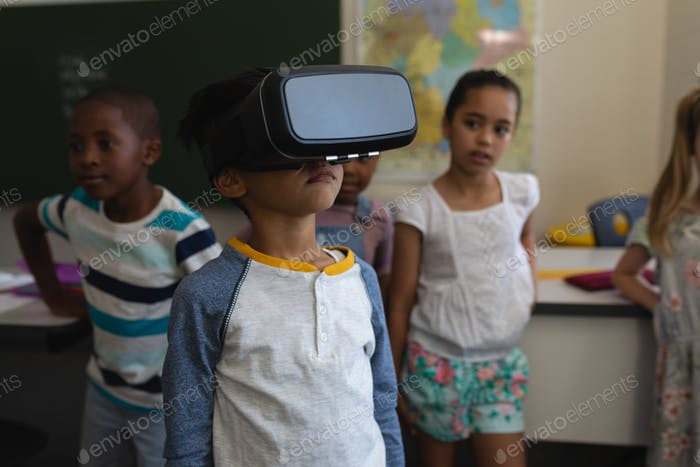 Schoolboy using virtual reality headset whit his classmates in classroom of elementary school