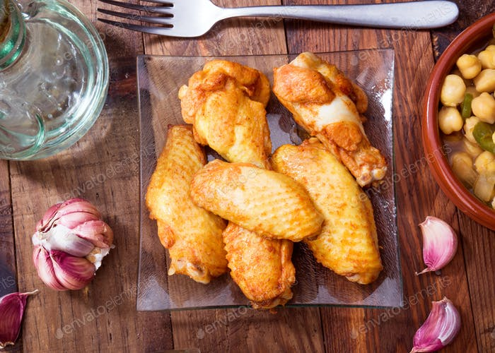 chicken wings cooked on rustic wooden board