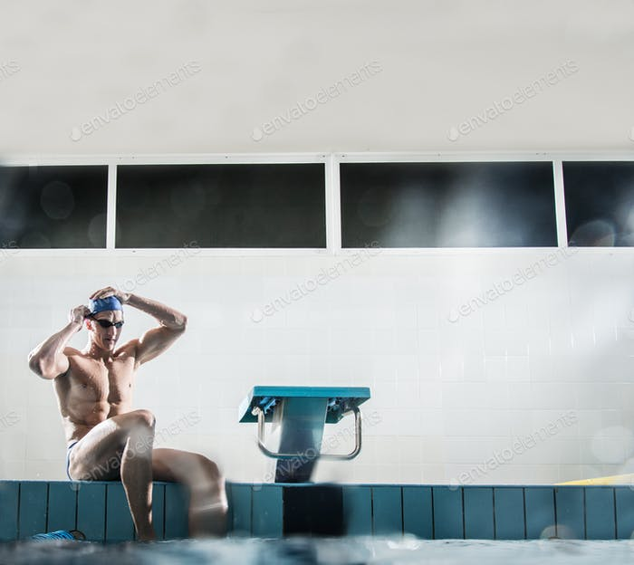 Young muscular swimmer putting on swimming goggles