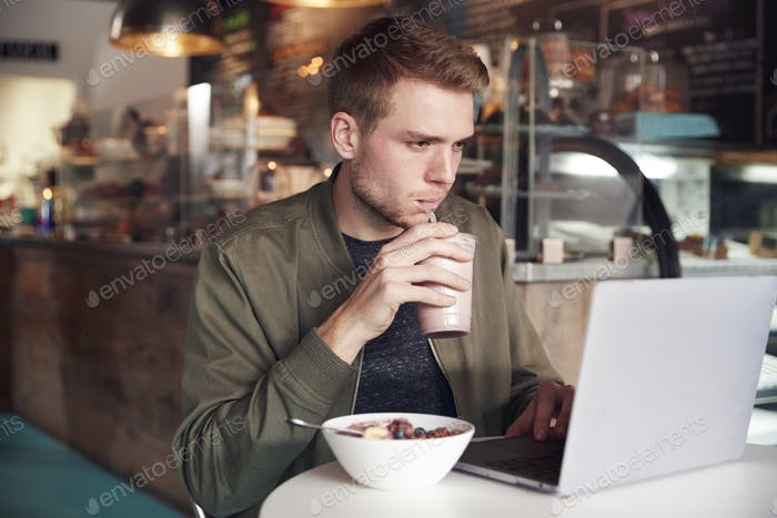 Young Man Using Laptop In Cafe Whilst Eating Breakfast