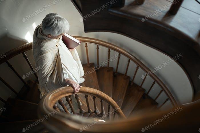 Sacerdote bajando las escaleras