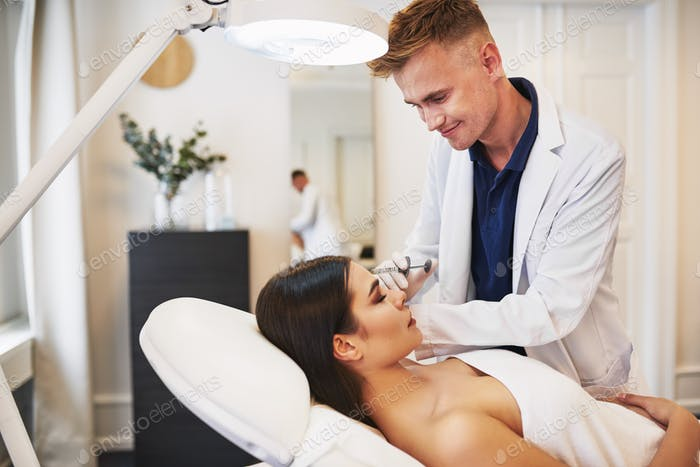 Smiling young doctor doing botox injections on a female client