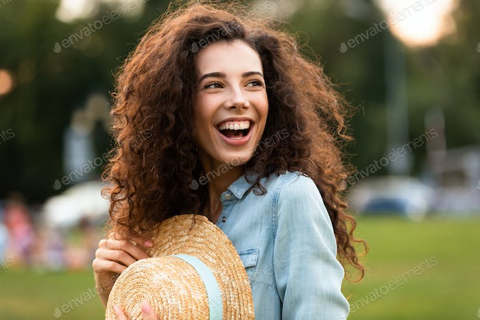 Image of attractive woman 20s holding straw hat and laughing, wh