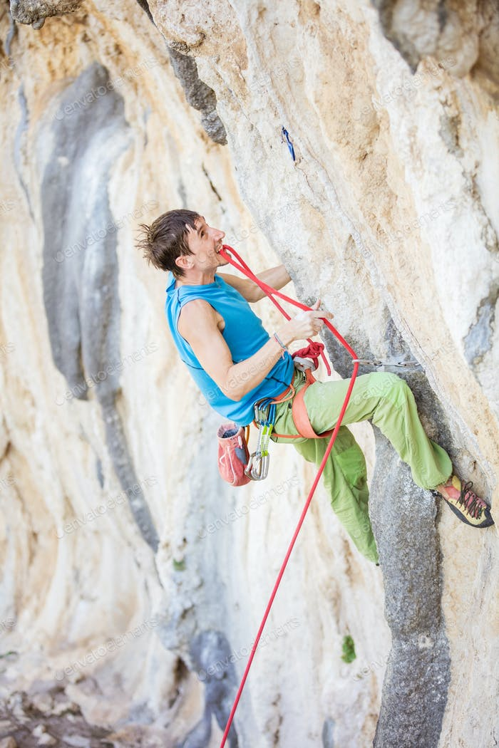 Young man going to clip rope while climbing challenging route on cliff