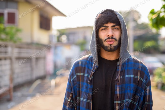 Young handsome bearded Indian hipster man in the city streets