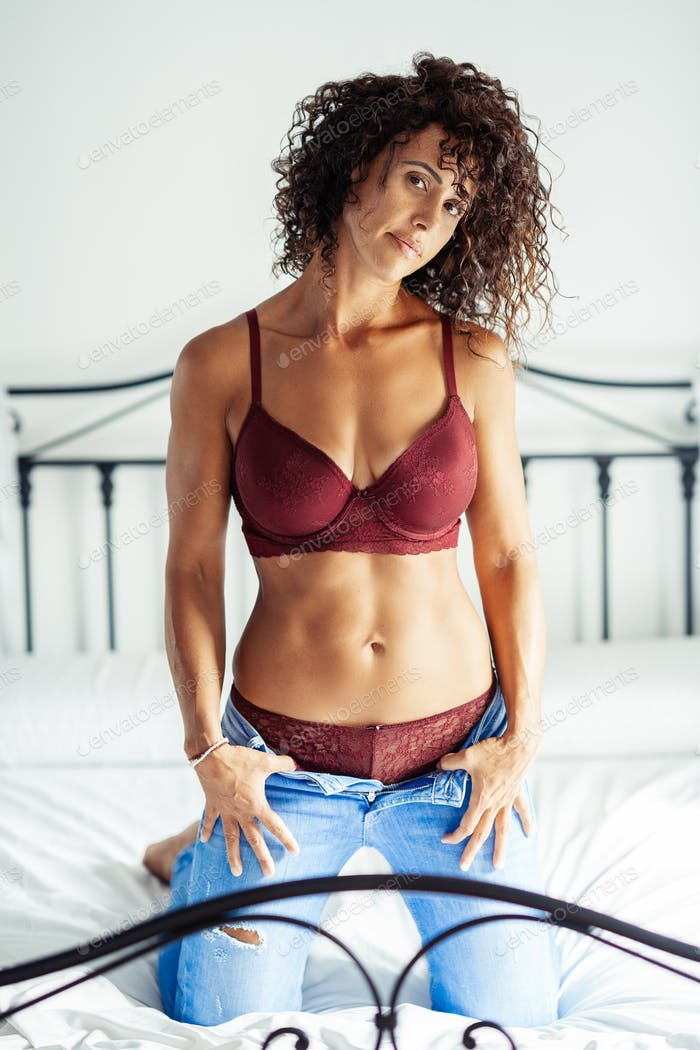 Middle-aged woman posing in bra and jeans