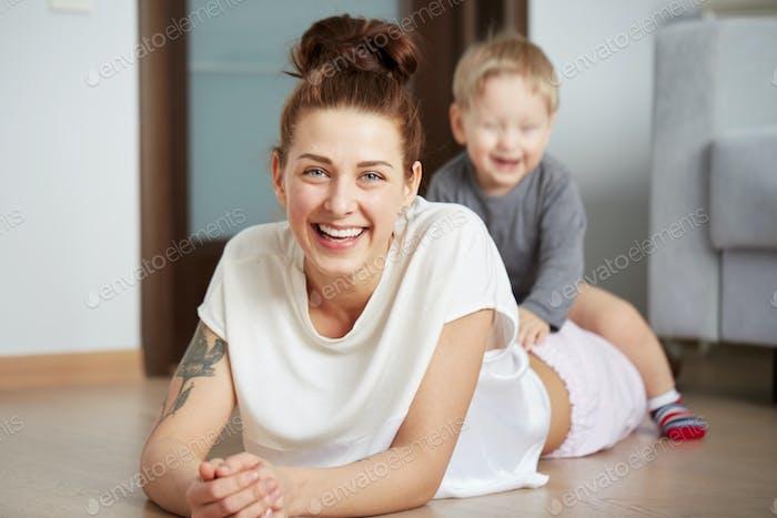 Joven madre con su hijo de un año vestido con pijama se relajan y jugando en el ser