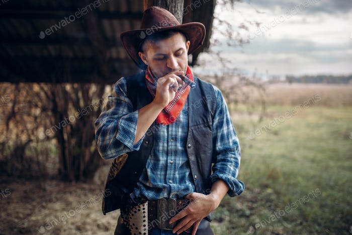 Brutal cowboy smokes a cigar, wild west culture