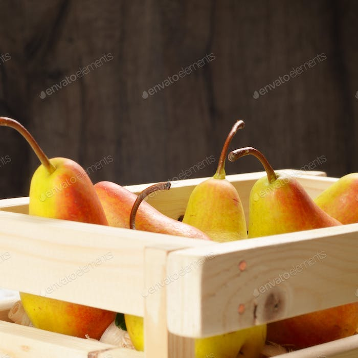 Wooden crate with pears on white table