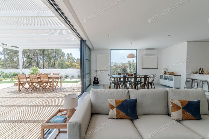 Living room in modern villa with and deck outside