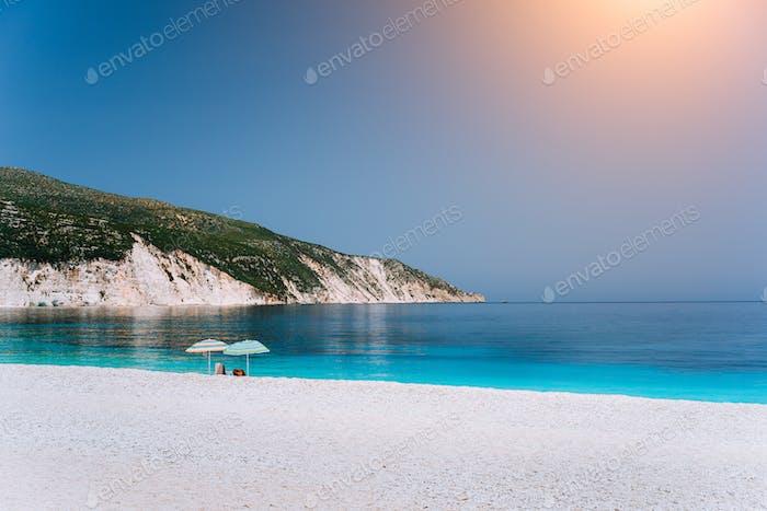 Sun beach umbrellas on a pebble beach with azure blue calm sea, white rocks and clear sky in