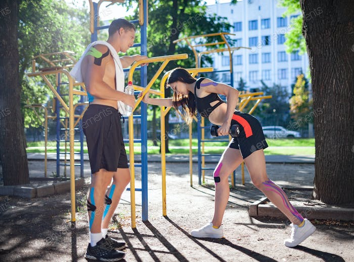 Couple with kinesiological elastic taping at sports ground
