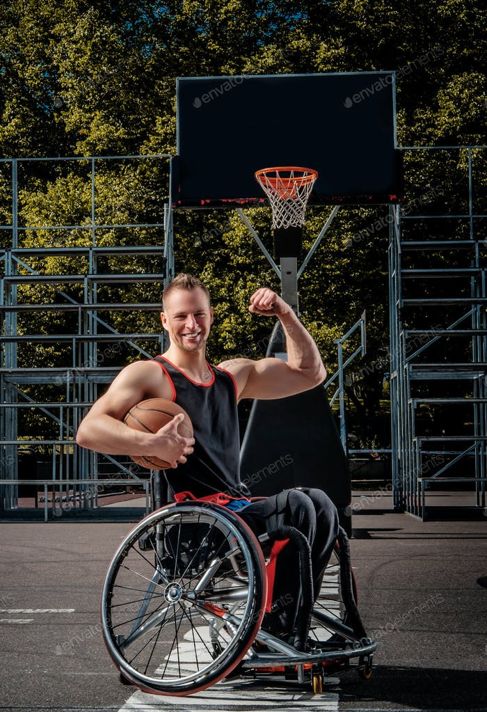 Happy basketball player in wheelchair pose with a ball on open gaming ground.