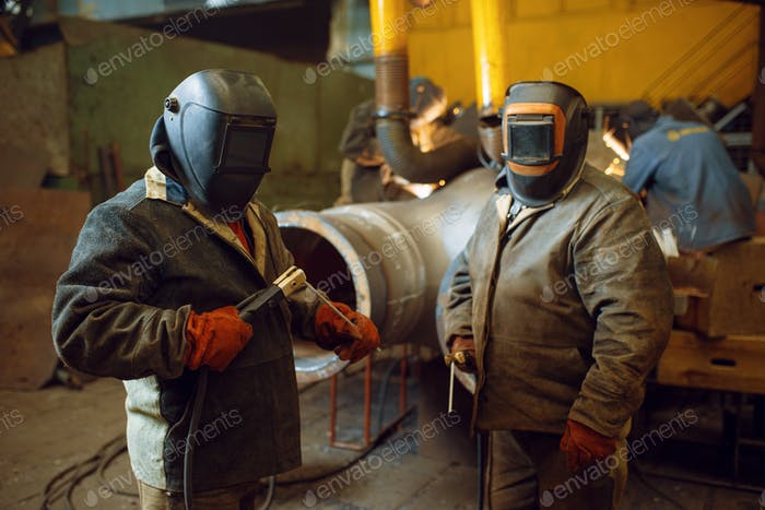 Two welder in masks prepares to work with metal