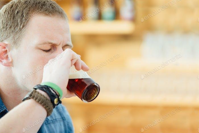 Man enjoying taste of dark beer