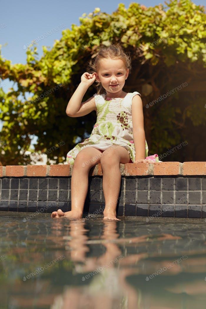Niedlich kleines Mädchen sitzt am Rande eines Swimmingpools