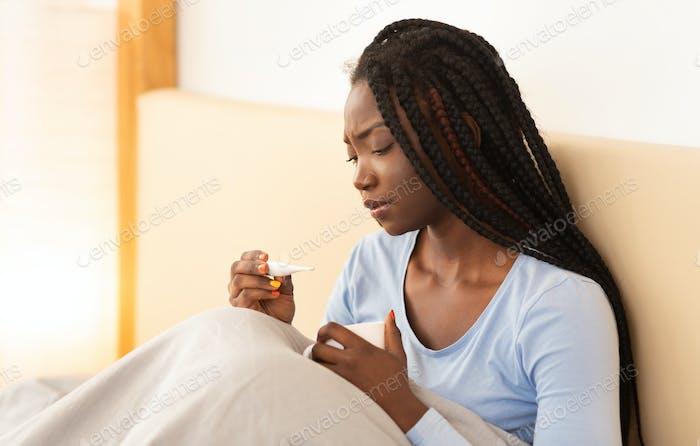 African American Mädchen mit Fieber halten Thermometer sitzen im Bett