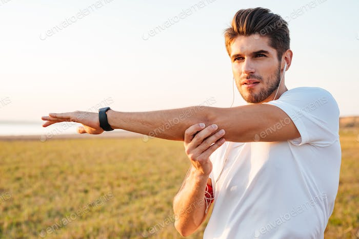 Concentrated sportsman stretching hands and listening to music with earphones