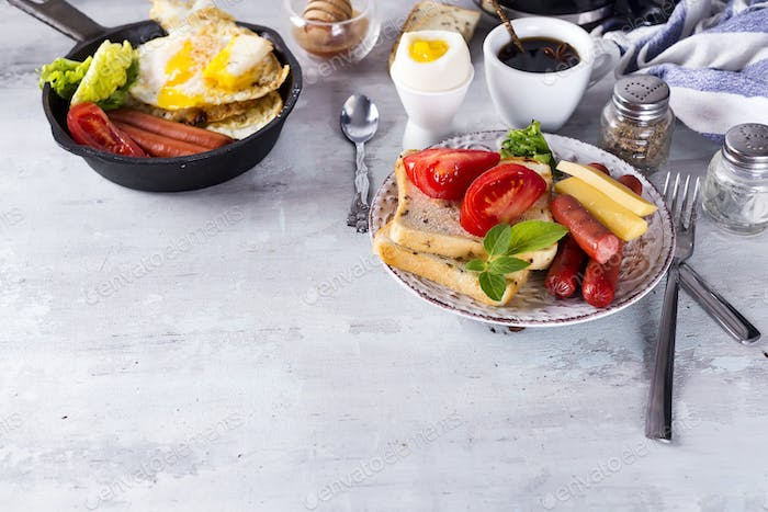 English breakfast. Fried eggs, sausages, toasts, tomatoes on stone table.