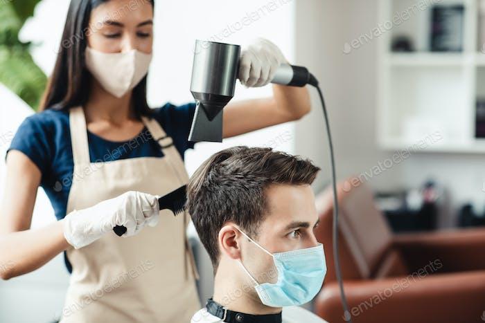 Friseur in Schutzmaske Herstellung Frisur für männliche Kunden, sterben seine Haare