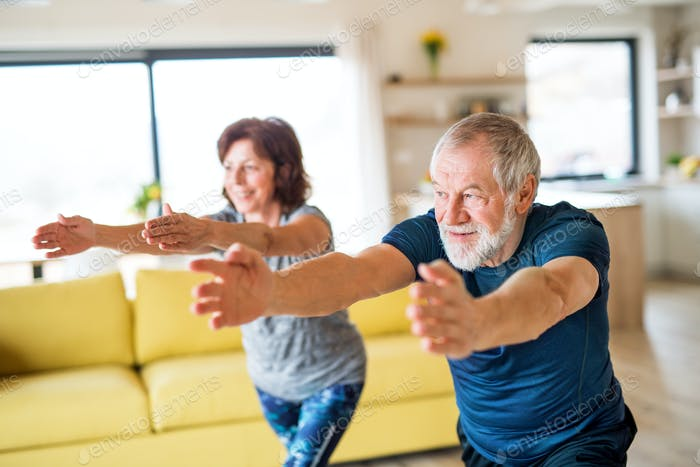A senior couple indoors at home, doing exercise indoors
