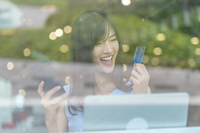 Asiatische Frau benutzt Kreditkarte mit Handy zum Online-Shopping