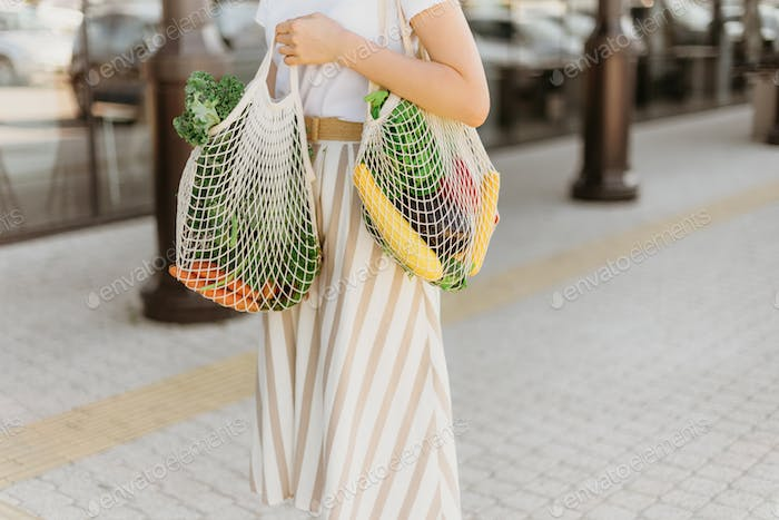 Zero waste concept with copy space. Woman holding cotton shopper and reusable mesh shopping bags