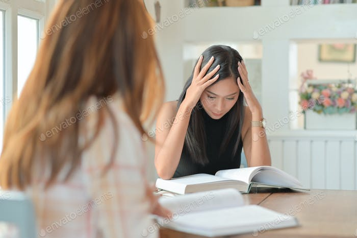 Two Asian female students are reading hard to prepare for university studies.