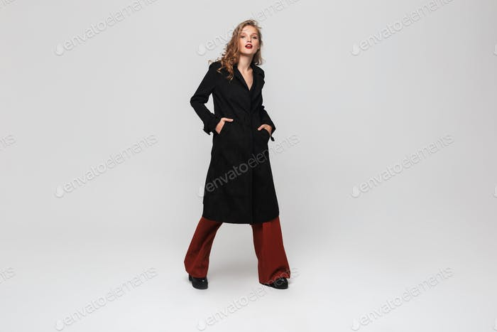 Young gorgeous woman with wavy hair in black coat and red wide trousers dreamily looking in camera