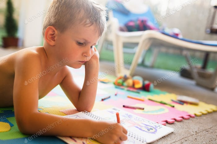 Picture of little boy drawing with crayons