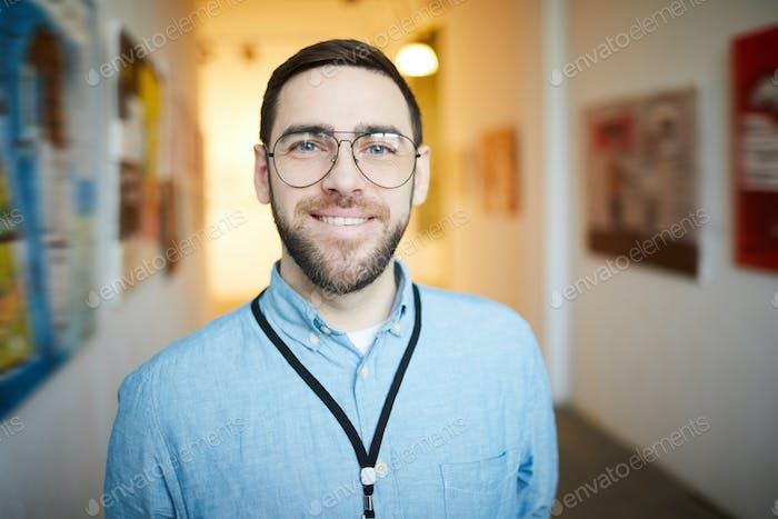 Smiling Bearded Man in Art Gallery