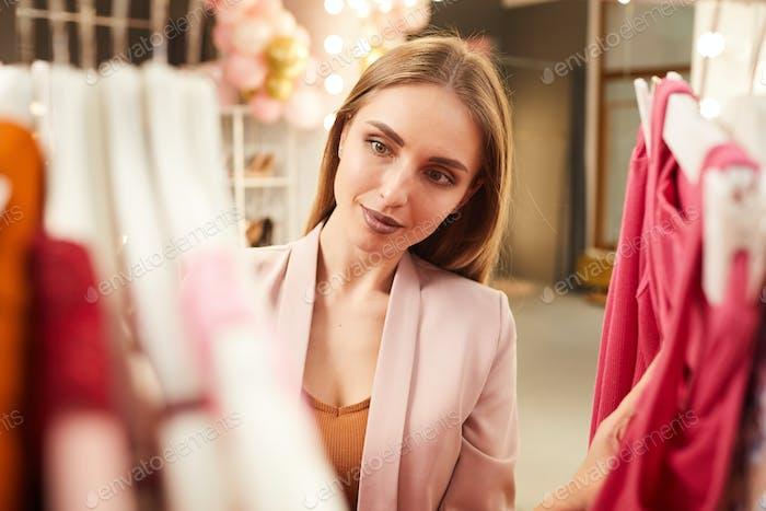 Beautiful Woman Choosing Dresses in Boutique