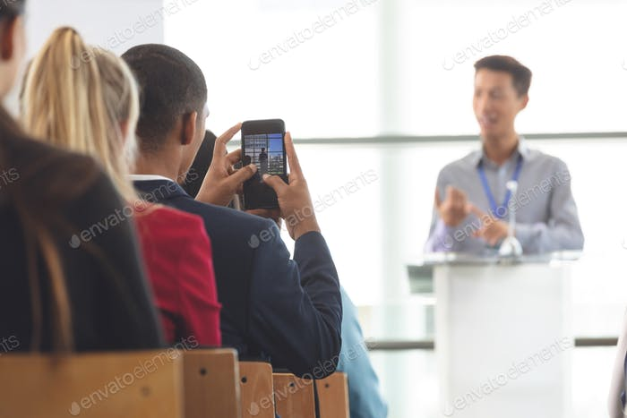 Businessman taking photo of businessman with mobile phone during seminar in office building