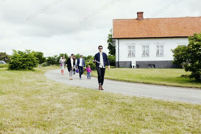Family walking on street by grassy field against cloudy sky
