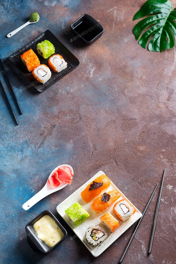 Various Fresh and delicious sushi set on black slate with slate sticks, sauce and nori on duotone
