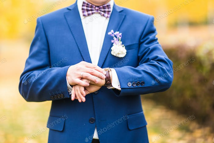 Man in suit checking time on his wrist watch